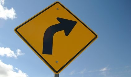 This is a yellow road sign with a black arrow indicating there is a sharp turn to the right ahead. The sign is clean and appears to be new. Nice blue sky with clouds in the background.